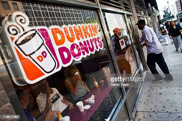 A customer enters a Dunkin' Donuts store in midtown Manhattan on July 11 2011 in the New York City Dunkin' Brands Group Inc the parent of Dunkin'...