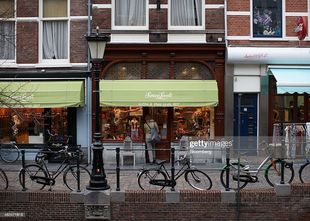 A customer enters a Simon Levelt coffee and tea shop as bicycles sit outside in Utrecht, Netherlands, on Friday, Nov. 29, 2013. European government bonds were little changed as investors showed a muted reaction to Standard & Poor's decision to raise its outlook on Spain's debt and strip the Netherlands of its top credit rating. Photographer: Jasper Juinen/Bloomberg via Getty Images