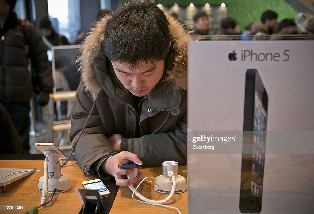 A customer examines the Apple Inc. iPhone 5 at a KT Corp. Olleh brand mobile phone store in Seoul, South Korea, on Friday, Dec. 7, 2012. The iPhone 5 went on sale in South Korea today. Photographer: Jean Chung/Bloomberg via Getty Images