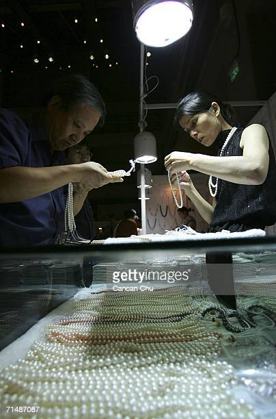 A customer examins a necklace of pearls at the Beijing International Jewelry Fair on July 20 2006 in Beijing China According to the Gemological...