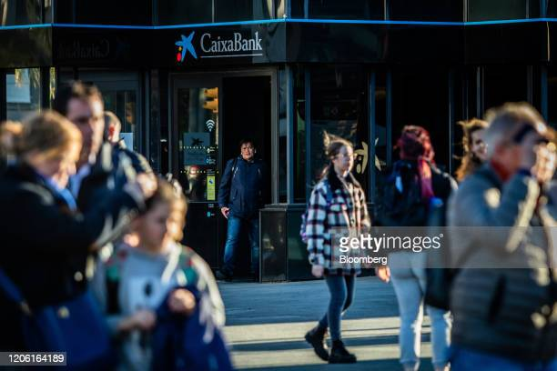 A customer exits a CaixaBank SA bank branch in Barcelona Spain on Thursday March 5 2020 Spanish bank shares soared after the European Unions top...