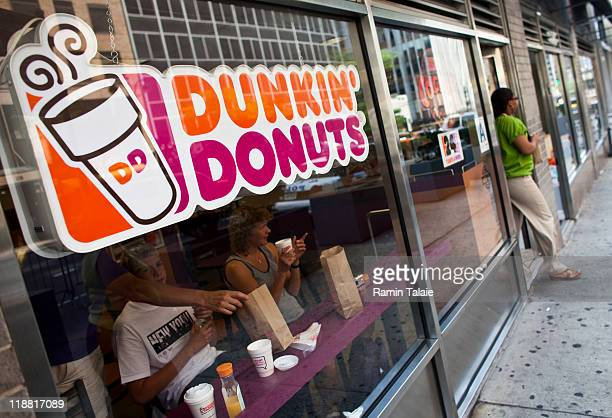 A customer exits a Dunkin' Donuts store in midtown Manhattan on July 11 2011 in the New York City Dunkin' Brands Group Inc the parent of Dunkin'...