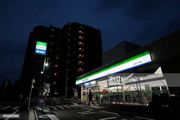 A customer exits a FamilyMart Co convenience store at dusk in Tokyo Japan on Saturday March 7 2015 FamilyMart and Uny Group Holdings Co are in merger...