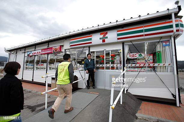 A customer exits a Seven I Holdings Co temporary 7Eleven convenience store in an area damaged by the tsunami following the Great East Japan...