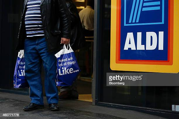 A customer exits an Aldi Stores Ltd supermarket with shopping bags in the Kilburn district of London UK on Monday Dec 22 2014 German discounters Aldi...