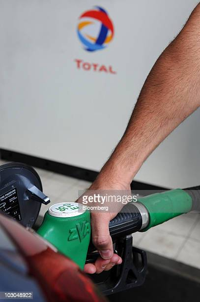 A customer fills his car with fuel at a Total SA gas station in Paris France on Thursday July 22 2010 The company Europe's biggest oil refiner...