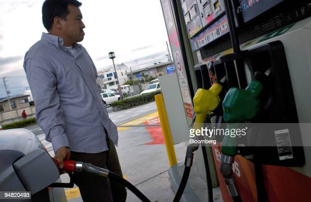 A customer fills his car with gas at a Nippon Oil Corp service station Tuesday March 29 2005 on the outskirts of Tokyo Confidence among Japan's large...