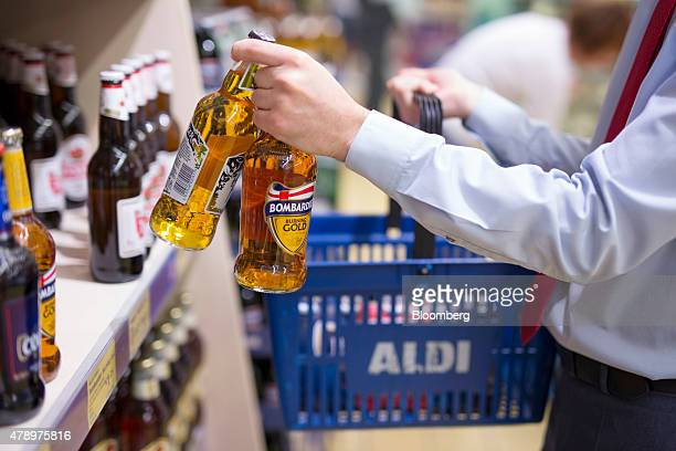 A customer fills his shopping basket with two bottles of Bombardier Burning Gold beer brewed by Wells Young's Brewing Company Ltd inside an Aldi...