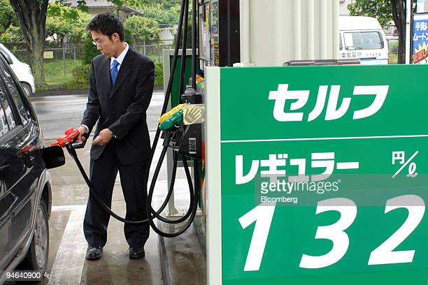 A customer fills his tank behind a board showing petrol prices at an Eneos gas station in Tokyo Japan Friday May 19 2006