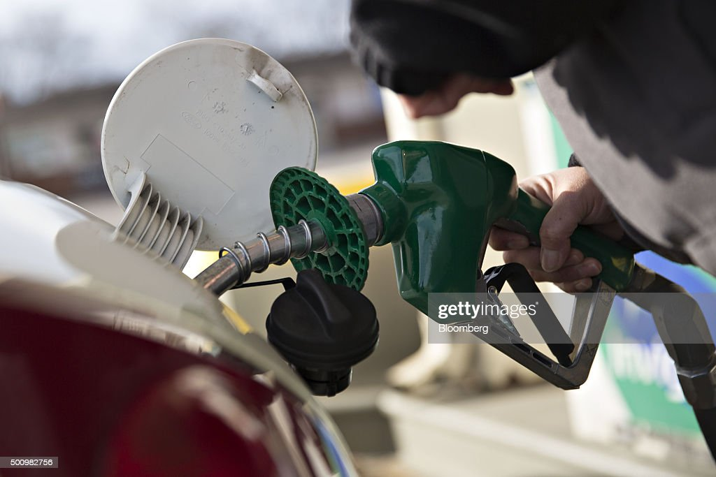 A customer fills their vehicle with fuel at a gas station in Chillicothe, Illinois, U.S., on Friday, Dec. 11, 2015. The cost of a gallon of regular gasoline fell 6.7 percent last month, based on data from motoring group AAA. Photographer: Daniel Acker/Bloomberg via Getty Images