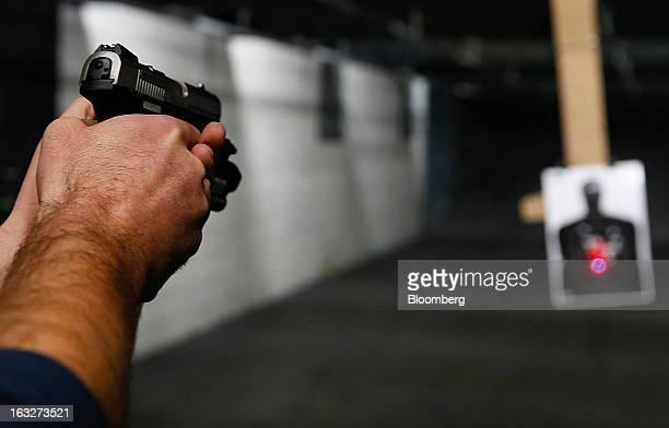A customer fires a Ruger SR9 9mm handgun at the Rangemasters of Utah gun range in Springville Utah US on Thursday Feb 28 2013 President Barack Obama...