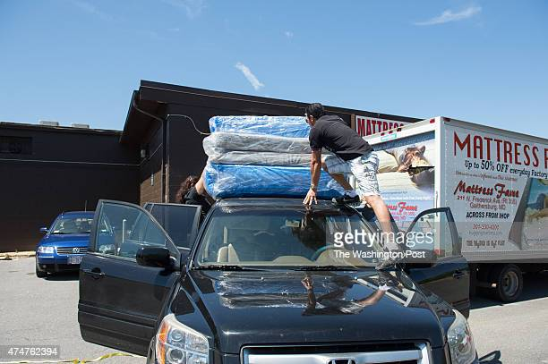 Customer Freddie Cataneda ties mattresses to the roof of his car after purchasing them from Mattress Fame on May 23 2015 in Rockville MD On the...