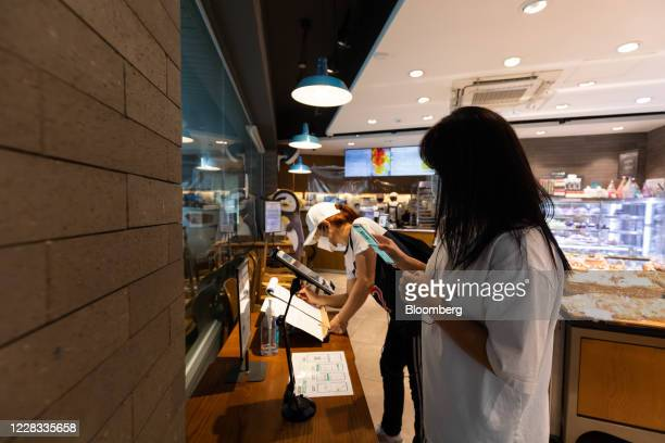 Customer, front, has her personal QR code scanned as another opts to write down her personal information on paper to log her entry at a bakery in...