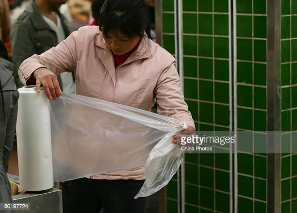 A customer gets a free plastic bag at a supermarket on March 11 2008 in Chongqing Municipality China The Chinese government has announced a...