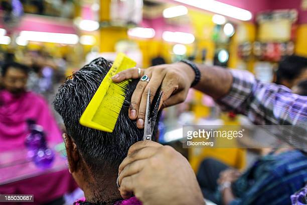 A customer gets a haircut at a barber's shop in Bangalore India on Friday Oct 11 2013 Reserve Bank of India Governor Raghuram Rajan has turned the...