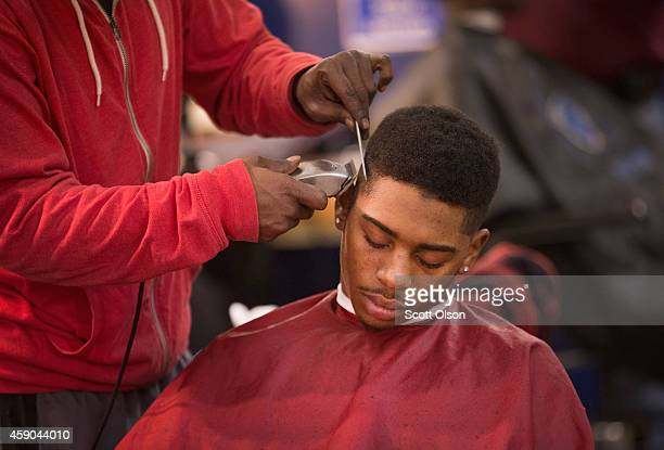 A customer gets a haircut at the Prime Time Barber and Beauty shop on West Florissant Street November 15 2014 in Ferguson Missouri Business has...