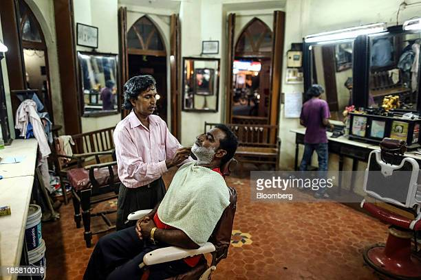 A customer gets a shave at a barber's shop in Calangute Goa India on Wednesday Oct 23 2013 Reserve Bank Of India Governor Raghuram Rajan told...