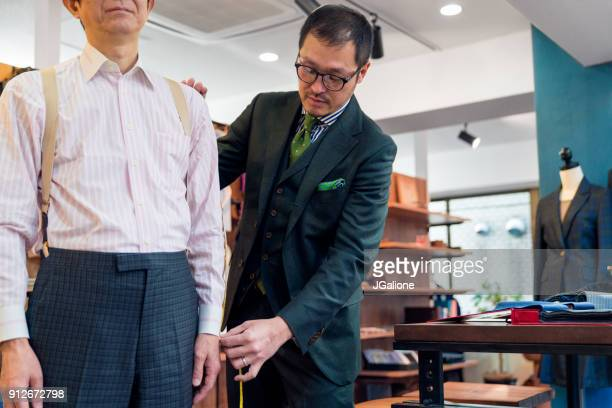 Customer getting measured by a tailor in a high end suit store