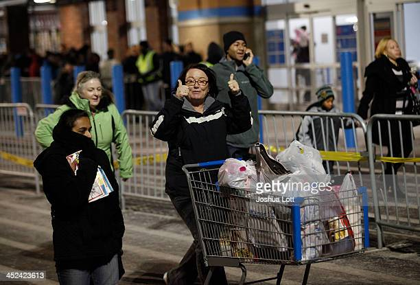 A customer gives the thumbsup as she leaves with her purchased items outside WalMart Thanksgiving day on November 28 2013 in Troy Michigan Black...