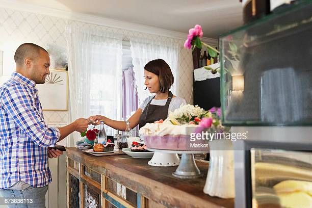 Customer giving credit card to female owner at cafe counter