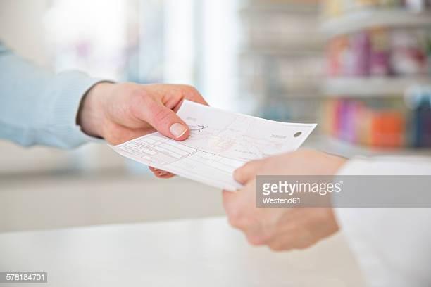 Customer giving prescription to female pharmacist