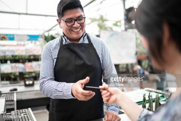 customer giving the credit card on checkout counter at small business - checkout stock pictures, royalty-free photos & images