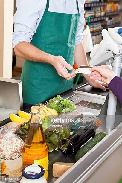 A customer handing a cashier a credit card at the supermarket