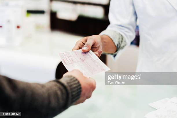 customer handing prescription to pharmacist - prescription stock pictures, royalty-free photos & images