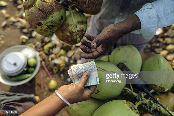 Customer hands an Indian one-hundred rupee banknote to a coconut vendor in Nagapattinam, Tamil Nadu, India, on Sunday, Oct. 16, 2016. India's new...
