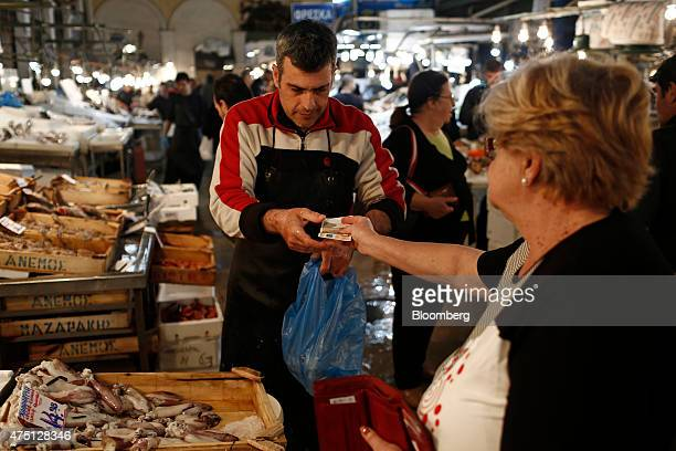 A customer hands over a 50 euro banknote to pay for fresh fish at a stall in the Varvakeios fish and meat market in Athens Greece on Friday May 29...