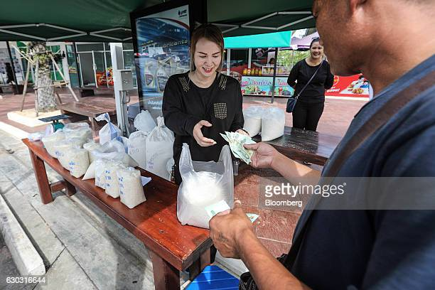 A customer hands over Thai baht banknotes to farmer Suphatson Chanthamon center at her rice stall in a PTT Pcl gas station in Ubon Ratchathani...