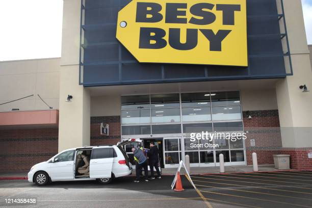 A customer has a new television delivered to his vehicle at a Best Buy store on March 23 2020 in Melrose Park Illinois Best Buy has closed all of it...