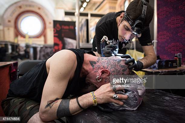 A customer has a piece of art tattooed onto his head at the Great British Tattoo Show in Alexandra Palace north London on May 23 2015 Taking place on...