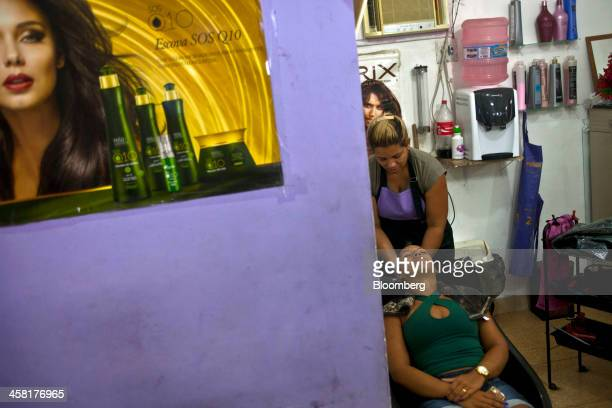 A customer has her hair colored at a beauty salon in the Complexo do Alemao shantytown in Rio de Janeiro Brazil on Tuesday Dec 17 2013 During...