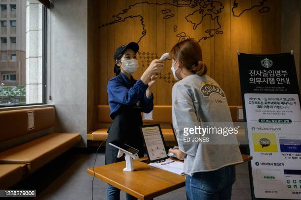Customer has her temperature checked as a preventative measure against the COVID-19 coronavirus inside a cafe in Seoul on August 31, 2020. - South...