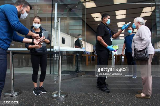 Customer has her temperature tested prior to entering the Apple Store at Bondi Junction on May 07, 2020 in Sydney, Australia. Apple stores across...