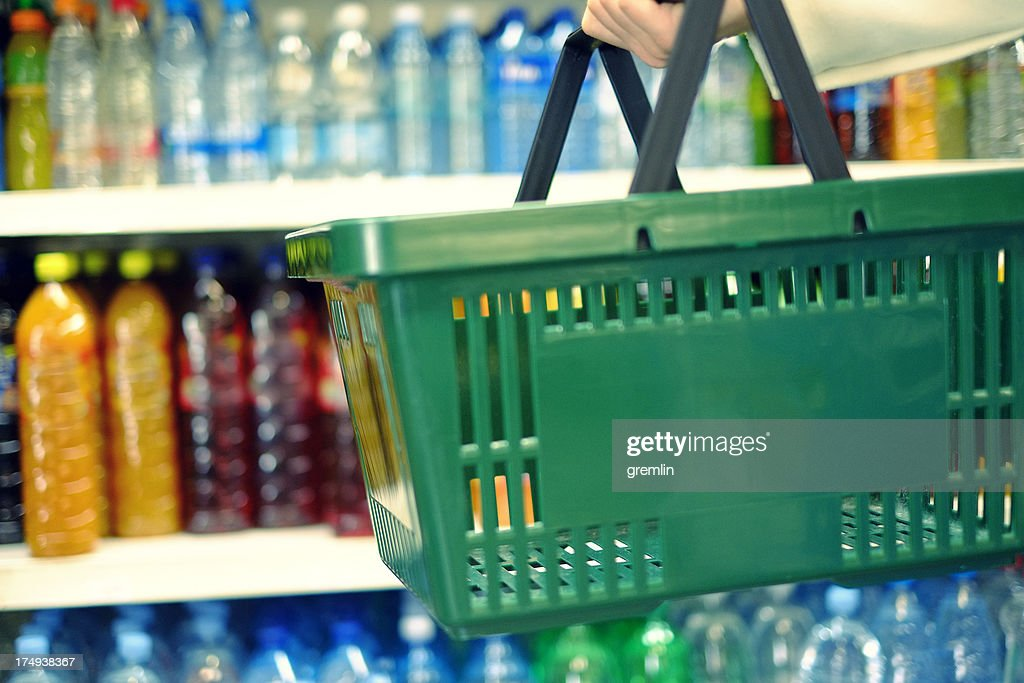 Customer holding shopping basket in the food store : Stock Photo