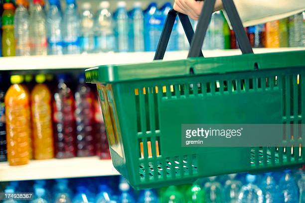 customer holding shopping basket in the food store - convenience store stock photos and pictures