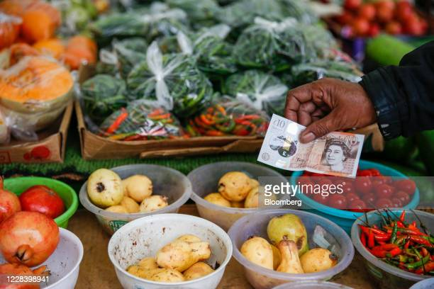 Customer holds a 10-pound banknote over fruit and vegetables in an arranged photograph at Chrisp Street Market in Poplar, London, U.K., on Thursday,...