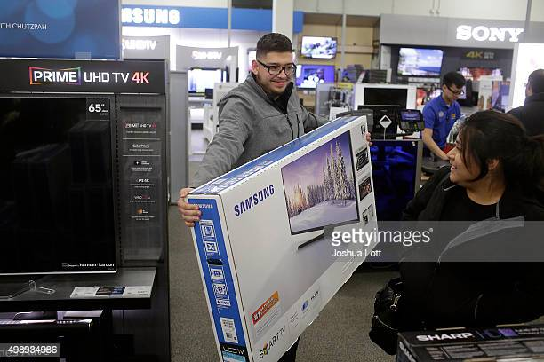 A customer holds a 48inch television at a Best Buy on November 27 2015 in Skokie Illinois Many retail business across the country offer deep...