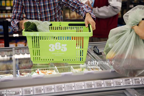 A customer holds a basket while shopping on the opening day of the 365 by Whole Foods Market store in the Silver Lake neighborhood of Los Angeles...