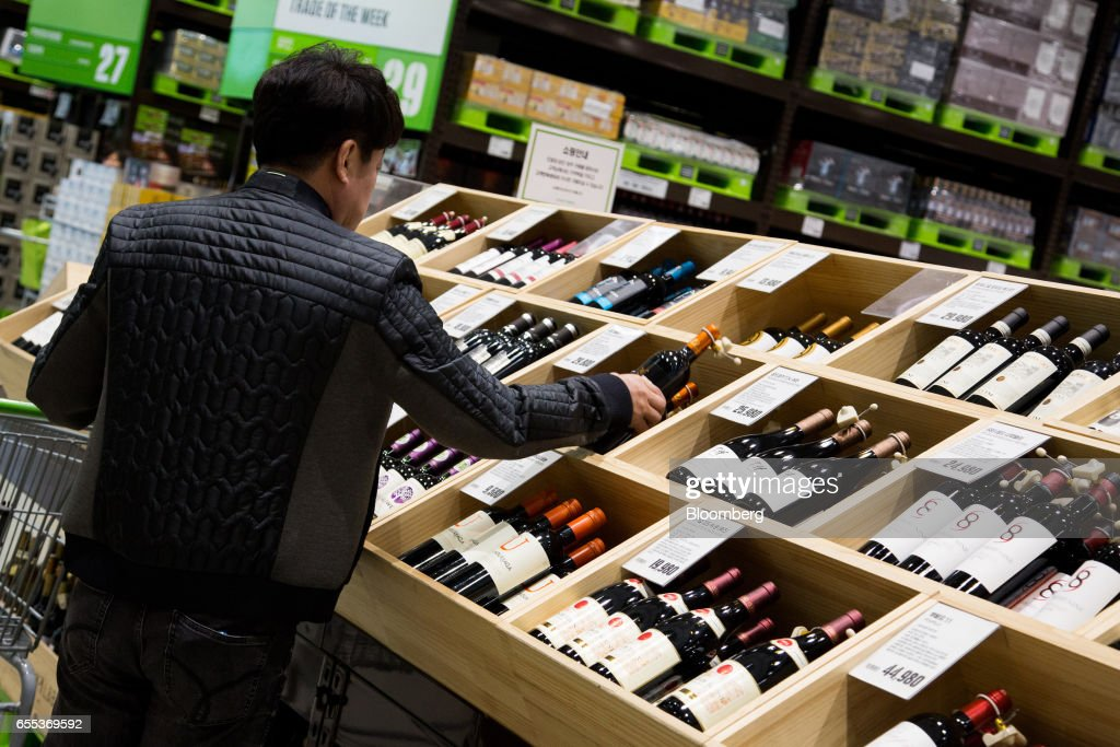 A customer holds a bottle of wine at an E-Mart Inc. Traders store in the Starfield Hanam shopping complex, operated by Shinsegae Co., in Hanam, Gyeonggi, South Korea, on Wednesday, March 15, 2017. Photographer: SeongJoon Cho/Bloomberg via Getty Images