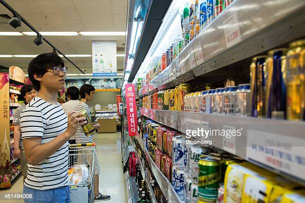 A customer holds a can of Miller Brewing Co beer at an EMart Co store a subsidiary of Shinsegae Co in Seoul South Korea on Friday June 27 2014 South...