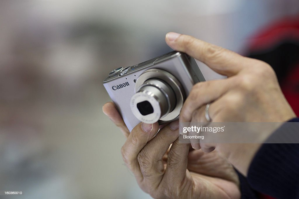 A customer holds a Canon Inc. PowerShot S110 digital compact camera at the company's showroom in Hong Kong, China, on Tuesday, Jan. 29, 2013. Canon, the world's largest camera maker, forecast profit will rise 14 percent this year amid a weaker yen and the withering of a boycott of Japanese goods in China. Photographer: Jerome Favre/Bloomberg via Getty Images