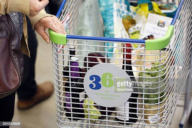 A customer holds a cart while shopping on the opening day of the 365 by Whole Foods Market store in the Silver Lake neighborhood of Los Angeles...