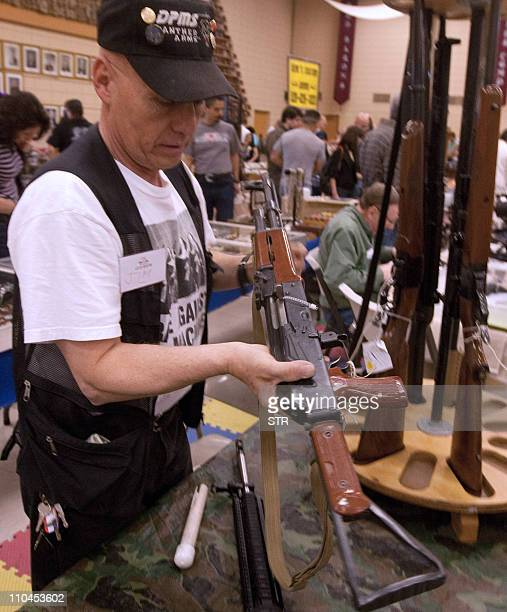 STORYA customer holds a Chinesemade AKM Type 56 assault rifle at a gun expo in El Paso Texas USA on March 13 2011 The Mexican authorities think that...