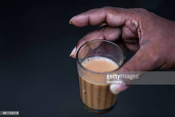 A customer holds a glass of chai at a roadside stall in Mumbai India on Friday Sept 25 2015 Chai the sweet milky tea concoction popular in most of...