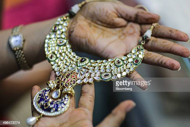 A customer holds a gold necklace for a photograph at the Umedmal Tilokchand Zaveri jewelry store during the festival of Dhanteras two days before...