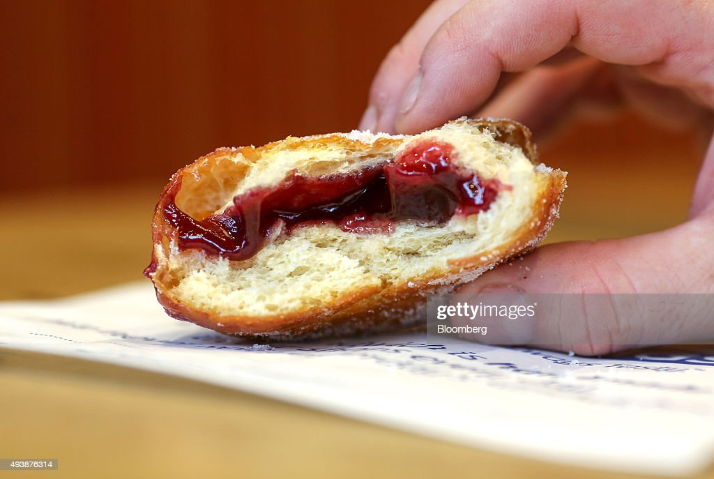 A customer holds a half finished jam doughnut inside a Greggs Plc sandwich chain outlet in Caterham, U.K., on Thursday, Oct. 22, 2015. Same-store sales at Greggs have grown 5.6 percent so far in 2015, up from 3.9 percent across the same period last year, and the company said on Oct. 6 that full-year growth will exceed its previous forecast slightly. Photographer: Chris Ratcliffe/Bloomberg via Getty Images