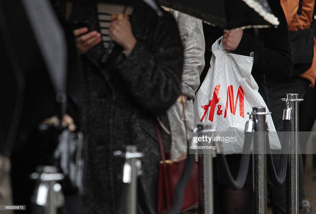 A customer holds a H&M carrier bag outside the new '& Other Stories' store operated by Hennes & Mauritz AB (H&M) on the launch day in London, U.K., on Friday, March 8, 2013. The Swedish retailer is diversifying with a sixth brand after falling behind larger competitor Inditex SA in the race for the price-sensitive fashionista's euro. Photographer: Chris Ratcliffe/Bloomberg via Getty Images